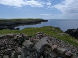 Broch ruins at Ardwell Bay with the Mull of Galloway in the distance.